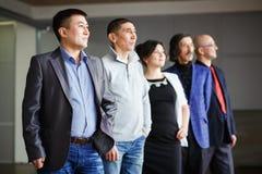 Η επιχειρησιακή ομάδα πέντε άνθρωποι, ένας άνδρας και μια γυναίκα που εξετάζουν την απόσταση, όλες είναι πίσω από τον ηγέτη τους  Στοκ Εικόνες