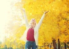 Η εποχή φθινοπώρου είναι ανοικτή! Πτώση φύλλων, ευτυχής νέα γυναίκα έκφρασης που έχει τη διασκέδαση θερμό σε ηλιόλουστο Στοκ Εικόνες