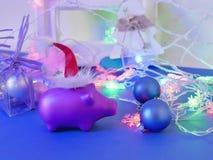 Η εποχιακή διακοσμητική σύνθεση από το χοίρο παιχνιδιών στο κόκκινο αισθάνθηκε το καπέλο Santa, ντεκόρ Χριστουγέννων, σφαίρες, δώ στοκ εικόνες