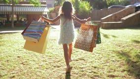 Η εποχιακή πώληση, λίγο κορίτσι αγοραστών με το μέρος των αγορών στα χέρια τρέχει κατά μήκος του χορτοτάπητα στον ήλιο φιλμ μικρού μήκους