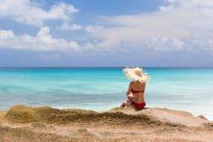 Η λεπτή γυναίκα στο κόκκινο μαγιό, κάθεται στη δύσκολη παραλία Στοκ Εικόνα