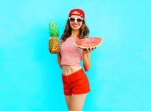 Η λεπτή χαμογελώντας γυναίκα μόδας αρκετά κρατά έναν ανανά και μια φέτα του καρπουζιού Στοκ φωτογραφία με δικαίωμα ελεύθερης χρήσης