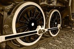 Η λεπτομέρεια σεπιών και κλείνει επάνω των τεράστιων ροδών σε ένα παλαιό locomo ατμού Στοκ Φωτογραφίες