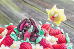 Η λεπτομέρεια σε ένα κέικ γενεθλίων για τα παιδιά με τις φράουλες και χαλά Στοκ Εικόνα