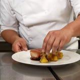 Η λεπτομέρεια του αρχιμάγειρα που διακοσμεί το παραδοσιακό περουβιανό γεύμα κάλεσε Chicharron de Panceta de Cerdo Στοκ φωτογραφία με δικαίωμα ελεύθερης χρήσης