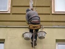 Η εργασία ατόμων για το πολυόροφο κτίριο λειτουργεί την επένδυση, επικονίαση του σπιτιού Στοκ Φωτογραφίες
