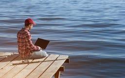 Η εργασία ατόμων ψαράδων για ένα lap-top, κάθεται σε μια ξύλινη αποβάθρα κοντά στη λίμνη, δίπλα σε την υπάρχει ένας πόλος αλιείας στοκ εικόνες