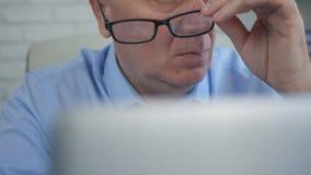Η εργασία γραφείων λήξης επιχειρηματιών παίρνει έξω τα γυαλιά του στοκ εικόνες