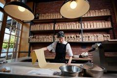 Η εργασία γυναικών με κυλημένος ζυμώνει Στοκ Φωτογραφίες