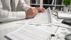Η εργασία επιχειρηματιών στο γραφείο και τη χρηματοδότηση υπολογισμού, διαβάζει και γράφει τις εκθέσεις έννοια επιχειρησιακής οικ φιλμ μικρού μήκους