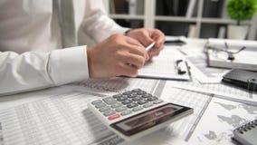 Η εργασία επιχειρηματιών στο γραφείο και τη χρηματοδότηση υπολογισμού, διαβάζει και γράφει τις εκθέσεις έννοια επιχειρησιακής οικ απόθεμα βίντεο