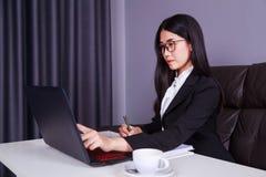 Η εργασία επιχειρησιακών γυναικών με το φορητό προσωπικό υπολογιστή και γράφει ένα περιοδικό Στοκ φωτογραφία με δικαίωμα ελεύθερης χρήσης