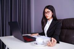 Η εργασία επιχειρησιακών γυναικών με το φορητό προσωπικό υπολογιστή και γράφει ένα περιοδικό Στοκ Εικόνα