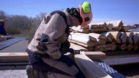 Η εργασία κάνει τις μετρήσεις με την ειδική συσκευή r Ο οικοδόμος στη μορφή και το κράνος κάνει τις μετρήσεις του ξύλινου πίνακα  απόθεμα βίντεο