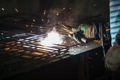 Η εργασία λειώνει τη σχάρα μετάλλων στην κατασκευή Στοκ Εικόνες