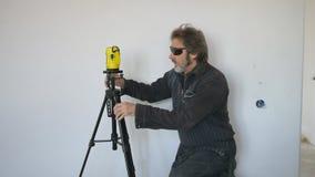Η εργασία με ένα επίπεδο λέιζερ κάνει τα σημάδια στον τοίχο Μηχανική ανύψωση Βίαιες συγκινήσεις απόθεμα βίντεο