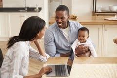 Η εργασία μητέρων από το σπίτι ως πατέρα κρατά την κόρη μωρών στοκ εικόνες