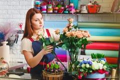 Η εργασία νέων κοριτσιών σε ένα ανθοπωλείο, γυναίκα ανθοκόμων κάνει μια ανθοδέσμη Στοκ φωτογραφία με δικαίωμα ελεύθερης χρήσης