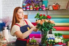 Η εργασία νέων κοριτσιών σε ένα ανθοπωλείο, γυναίκα ανθοκόμων κάνει μια ανθοδέσμη Στοκ Εικόνες