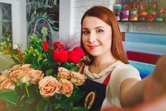 Η εργασία νέων κοριτσιών σε ένα ανθοπωλείο, Floristry κάνει selfie τη φωτογραφία με μια ανθοδέσμη των λουλουδιών Στοκ φωτογραφία με δικαίωμα ελεύθερης χρήσης