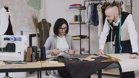 Η εργασία ομάδας δύο προσαρμόζει και μοδίστρα που είναι χαμόγελο και εργασία στο ράψιμο μιας νέας συλλογής Seamstress κόβει το σχ απόθεμα βίντεο