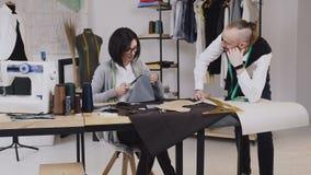 Η εργασία ομάδας δύο προσαρμόζει και μοδίστρα που είναι χαμόγελο και εργασία στο ράψιμο μιας νέας συλλογής Seamstress χάρασε το α απόθεμα βίντεο