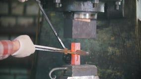 Η εργασία σιδηρουργών με το ηλεκτρικό σφυρί στο αμόνι, κλείνει αυξημένος του χεριού κάνοντας τη σωστή μορφή του κοκκίνου - καυτός απόθεμα βίντεο