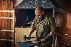 Η εργασία σιδηρουργών σφυρηλατεί Κατασκευή των μερών και των όπλων από το λειωμένο μέταλλο, που χρησιμοποιεί το σφυρί και το αμόν Στοκ Φωτογραφία