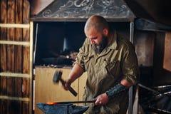 Η εργασία σιδηρουργών σφυρηλατεί Κατασκευή των μερών και των όπλων από το λειωμένο μέταλλο, που χρησιμοποιεί το σφυρί και το αμόν Στοκ Εικόνα