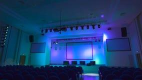 Η εργασία του εξοπλισμού φωτισμού ελέγχεται πριν από την έναρξη μιας μεγάλης συναυλίας στη σύγχρονη αίθουσα Τα πολύχρωμα φω'τα λά απόθεμα βίντεο