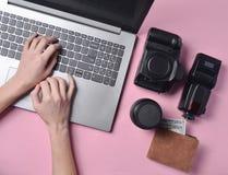 Η εργασία του φωτογράφου, φωτογραφιών Φωτογραφικός εξοπλισμός, θηλυκά χέρια που δακτυλογραφεί στο πληκτρολόγιο lap-top στη ρόδινη στοκ εικόνα με δικαίωμα ελεύθερης χρήσης