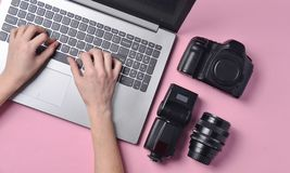 Η εργασία του φωτογράφου, φωτογραφιών Φωτογραφικός εξοπλισμός, θηλυκά χέρια που δακτυλογραφεί στο πληκτρολόγιο lap-top στοκ εικόνα