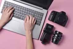 Η εργασία του φωτογράφου, φωτογραφιών Φωτογραφικός εξοπλισμός, θηλυκά χέρια που δακτυλογραφεί στο πληκτρολόγιο lap-top στοκ εικόνες