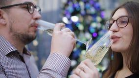 Η ερωτευμένη σαμπάνια κατανάλωσης ζεύγους, κάνει μια επιθυμία και φιλά τις διακοσμήσεις Χριστουγέννων Φιλί στο υπόβαθρο φιλμ μικρού μήκους