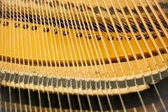 Η εστίαση μέσα του μεγάλου πιάνου, παρουσιάζει σειρές πιάνων που κάνουν τη μουσική το υγιές κλειδί Στοκ Εικόνες