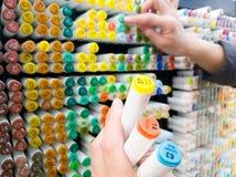 Η εστίαση στη λαβή χεριών γυναικών η επιλεγμένη μάνδρα χρώματος με άλλο χέρι επιλέγει τη μάνδρα χρώματος στο ράφι στο κατάστημα χ Στοκ φωτογραφία με δικαίωμα ελεύθερης χρήσης