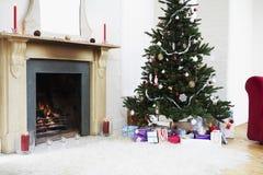 Η εστία και το χριστουγεννιάτικο δέντρο με παρουσιάζουν στοκ εικόνες