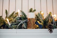 Η εστία Χριστουγέννων, διακόσμηση φω'των Χριστουγέννων, δέντρο διακλαδίζεται, κεριά και κομμάτια πεύκων Στοκ Φωτογραφίες
