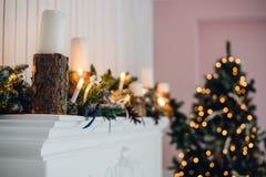 Η εστία Χριστουγέννων, διακόσμηση φω'των Χριστουγέννων, δέντρο διακλαδίζεται, κεριά και κομμάτια πεύκων Στοκ εικόνα με δικαίωμα ελεύθερης χρήσης