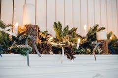 Η εστία Χριστουγέννων, διακόσμηση φω'των Χριστουγέννων, δέντρο διακλαδίζεται, κεριά και κομμάτια πεύκων Στοκ Εικόνες