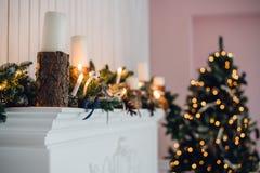 Η εστία Χριστουγέννων, διακόσμηση φω'των Χριστουγέννων, δέντρο διακλαδίζεται, κεριά και κομμάτια πεύκων Στοκ εικόνες με δικαίωμα ελεύθερης χρήσης