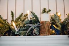 Η εστία Χριστουγέννων, διακόσμηση φω'των Χριστουγέννων, δέντρο διακλαδίζεται, κεριά και κομμάτια πεύκων Στοκ Φωτογραφία