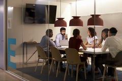 Η εταιρική ομάδα στον πίνακα σε έναν θαλαμίσκο αιθουσών συνεδριάσεων, κλείνει επάνω Στοκ Φωτογραφίες