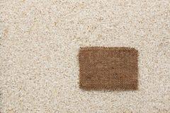 Η ετικέττα φιαγμένη από burlap βρίσκεται ενάντια στο σκηνικό του ρυζιού Στοκ Εικόνες
