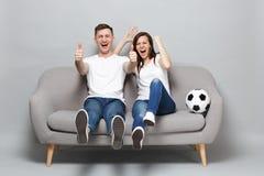 Η ευθυμία οπαδών ποδοσφαίρου ανδρών γυναικών ζευγών γέλιου υποστηρίζει επάνω την αγαπημένη ομάδα με τη σφαίρα ποδοσφαίρου, που πα στοκ φωτογραφία