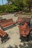 Η ευρεία άποψη της ομάδας μη κατειλημμένων ξύλινων καθισμάτων ή καρεκλών τακτοποίησε σε έναν κήπο ή ένα πάρκο, Chennai, Ινδία, τη στοκ εικόνες