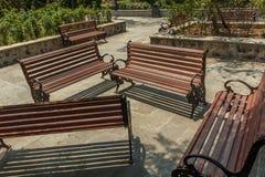 Η ευρεία άποψη της ομάδας μη κατειλημμένων ξύλινων καθισμάτων ή καρεκλών τακτοποίησε σε έναν κήπο ή ένα πάρκο, Chennai, Ινδία, τη στοκ φωτογραφίες