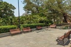 Η ευρεία άποψη της ομάδας μη κατειλημμένων ξύλινων καθισμάτων ή καρεκλών τακτοποίησε σε έναν κήπο ή ένα πάρκο, Chennai, Ινδία, τη στοκ εικόνα