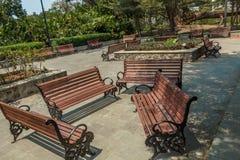 Η ευρεία άποψη της ομάδας μη κατειλημμένων ξύλινων καθισμάτων ή καρεκλών τακτοποίησε σε έναν κήπο ή ένα πάρκο, Chennai, Ινδία, τη στοκ εικόνα με δικαίωμα ελεύθερης χρήσης