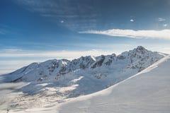 Η ευρεία πυροβοληθείσα εναέρια άποψη του χιονιού κάλυψε τα κρύα βουνά βράχου με τους ηλιόλουστους μπλε ουρανούς στοκ φωτογραφία με δικαίωμα ελεύθερης χρήσης